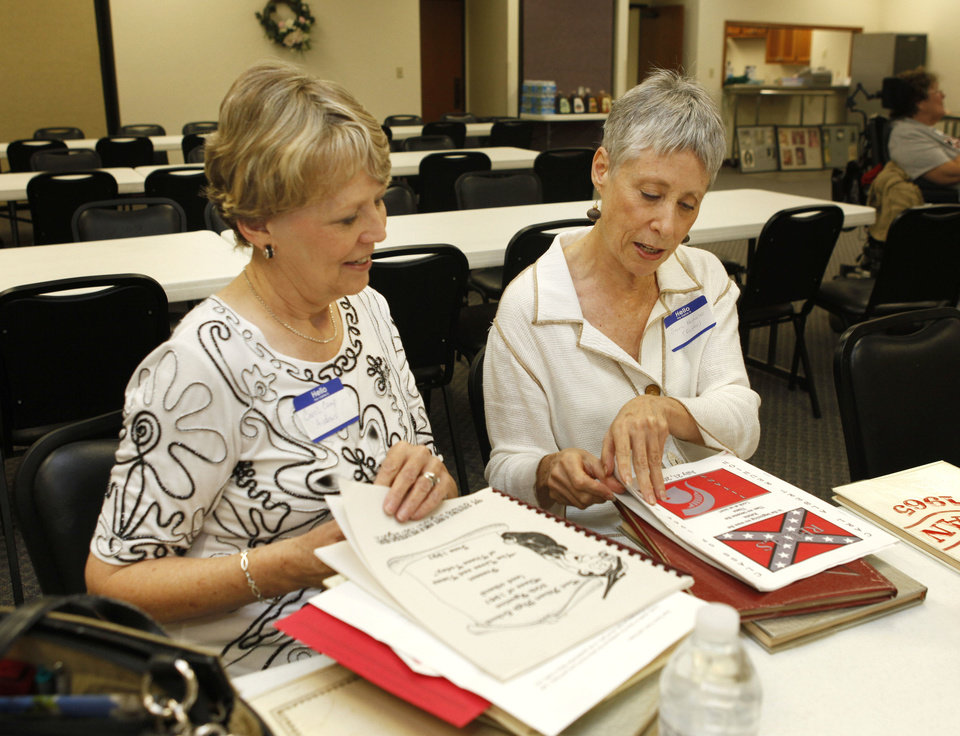Class of 1965 alumni Carol Camp Andrews, left, and Sacra Foster Nicholas look at memorabilia as Carl Albert High School alumni hold a get-together  Saturday. Photo by Paul Hellstern, The Oklahoman