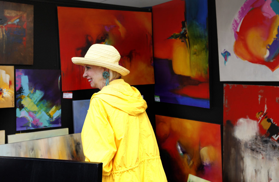 Photo - Joy Richardson works at her booth Sunday at the arts festival.