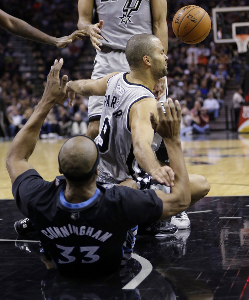 Photo - San Antonio Spurs' Tony Parker (9), of France, crashes into Minnesota Timberwolves' Dante Cunningham (33) while trying to score during the first half of an NBA basketball game on Sunday, Jan. 12, 2014, in San Antonio. Parker was called for charging.  (AP Photo/Eric Gay)