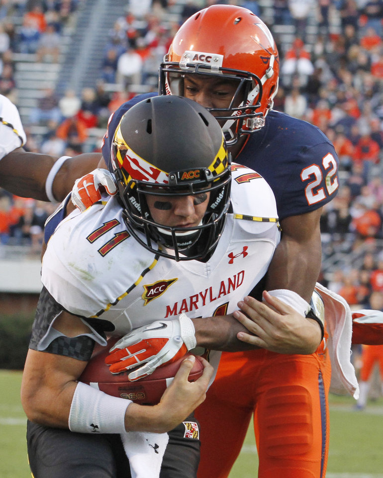 Photo -   Maryland quarterback Perry Hills (11) breaks the tackle of Virginia cornerback Drequan Hoskey (22) as he scores during the second half of an NCAA college football game in Charlottesville, Va., Saturday, Oct. 13, 2012. Maryland won 27-20. (AP Photo/Steve Helber)