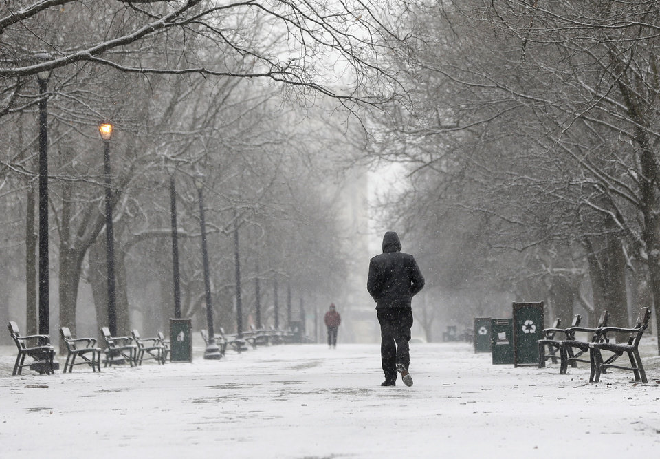 Photo - A pedestrian walks through the snow in Washington Park on Friday, Feb. 8, 2013, in Albany, N.Y. Parts of the New York region still cleaning up from Superstorm Sandy are bracing for a winter storm that's expected to blanket the Northeast with heavy snow Friday and Saturday. (AP Photo/Mike Groll)