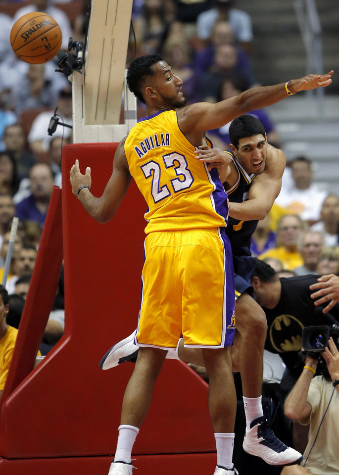 Photo -   Utah Jazz's Enes Kanter, right, passes the ball as he is defended by Los Angeles Lakers' Ronnie Aguilar during the first half of an NBA preseason basketball game in Anaheim, Calif., Tuesday, Oct. 16, 2012. (AP Photo/Jae Hong)