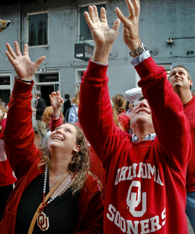 Photo - Sooner fans Claire and Herve Hosek(cq) try to catch beads thrown from the balconies on Bourbon Street before the start of the NCAA football BCS Sugar Bowl game between the University of Oklahoma Sooners (OU) and the University of Alabama Crimson Tide (UA) at the Superdome in New Orleans, La., Thursday, Jan. 2, 2014.  .Photo by Chris Landsberger, The Oklahoman