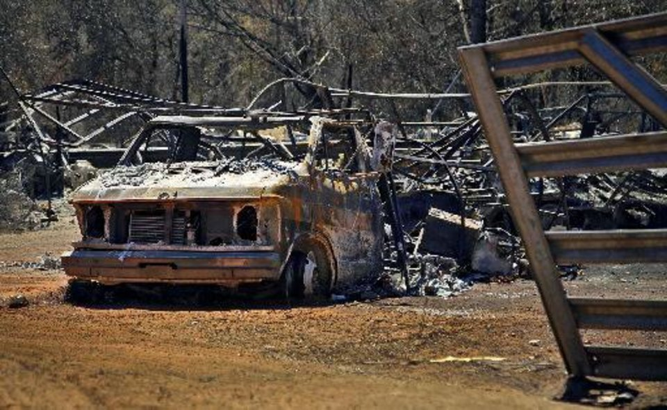 Photo - A burned out car is part of the damage left behind on Tuesday, Sept. 6, 2011, in Oklahoma City, Okla. after the wildfires that cut a path through northeast Oklahoma City.  Chris Landsberger