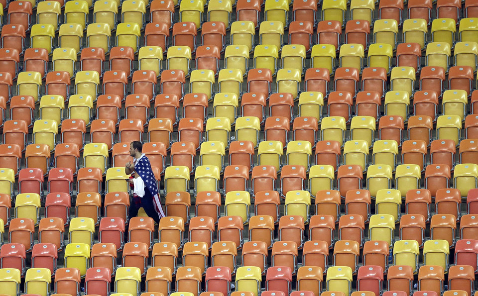 Photo - A US fan leaves the stands after a 2-2 draw in the group G World Cup soccer match between the USA and Portugal at the Arena da Amazonia in Manaus, Brazil, Sunday, June 22, 2014. (AP Photo/Themba Hadebe)