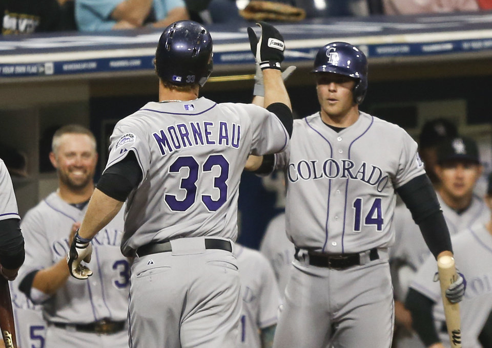 Photo - Colorado Rockies' Justin Morneau is greeted by Josh Rutledge, right, and Michael Cuddyer, left, after hitting a solo home run against the San Diego Padres in the second inning of a baseball game Wednesday, April 16, 2014, in San Diego.  (AP Photo/Lenny Ignelzi)