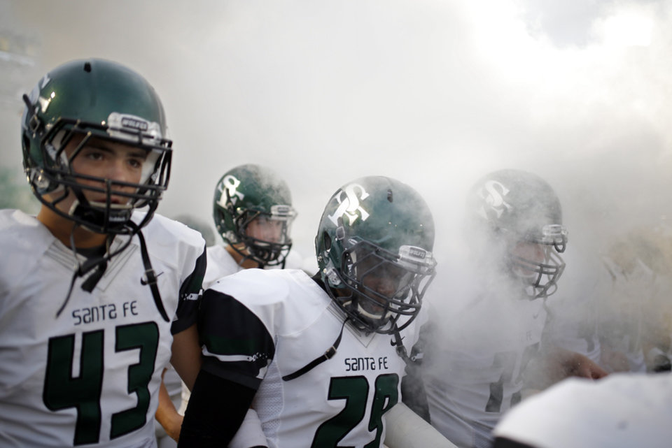 Photo - Edmond Santa Fe walks on to the field before the high school football game between Edmond North High School and Edmond Santa Fe High School at Wantland Stadium in Edmond, Okla.,  Friday, Sept. 20, 2013. Photo by Sarah Phipps, The Oklahoman