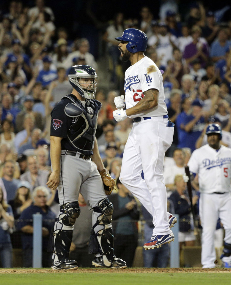 Photo - Los Angeles Dodgers' Matt Kemp, right, celebrates his second two-run home run of the game in front of Atlanta Braves catcher Evan Gattis during the seventh inning of a baseball game on Tuesday, July 29, 2014, in Los Angeles. (AP Photo/Jae C. Hong)