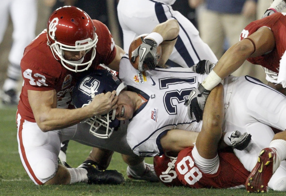 Photo - Oklahoma's Patrick O'Hara (43), left, and Oklahoma's Austin Haywood (89) bring down Connecticut's Nick Williams (31)during the Fiesta Bowl college football game between the University of Oklahoma Sooners and the University of Connecticut Huskies in Glendale, Ariz., at the University of Phoenix Stadium on Saturday, Jan. 1, 2011.  Photo by Bryan Terry, The Oklahoman