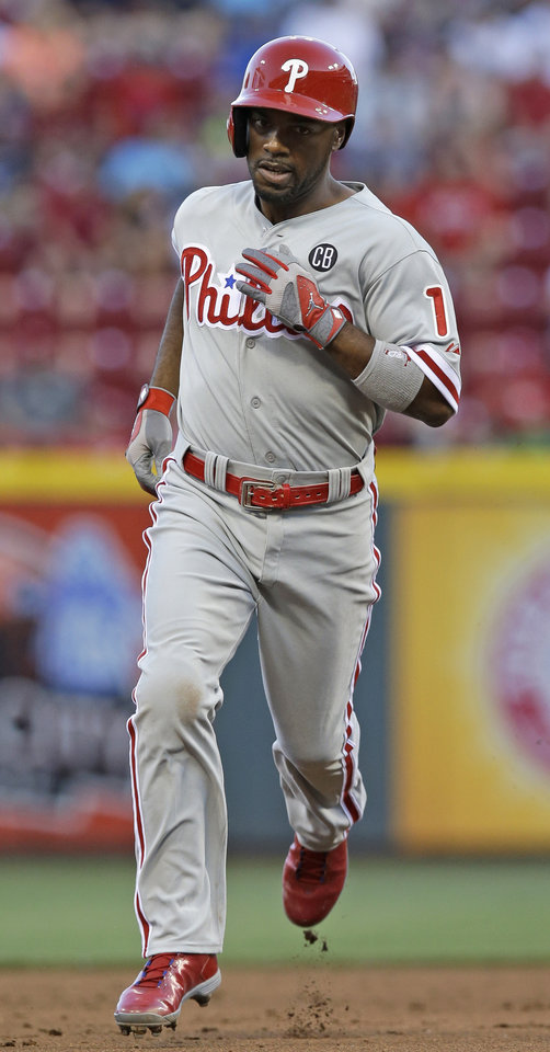 Photo - Philadelphia Phillies' Jimmy Rollins rounds the bases after hitting a solo home run off Cincinnati Reds starting pitcher Johnny Cueto in the fifth inning of a baseball game, Friday, June 6, 2014, in Cincinnati. (AP Photo/Al Behrman)