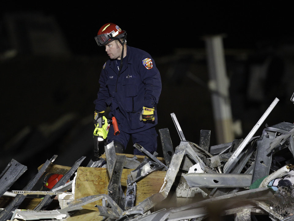 Photo - An emergency worker searches a Walmart store that was severely damaged by a tornado in Joplin, Mo., Monday, May 23, 2011. A large tornado moved through much of the city Sunday, damaging a hospital and hundreds of homes and businesses. (AP Photo/Charlie Riedel) ORG XMIT: MOCR101