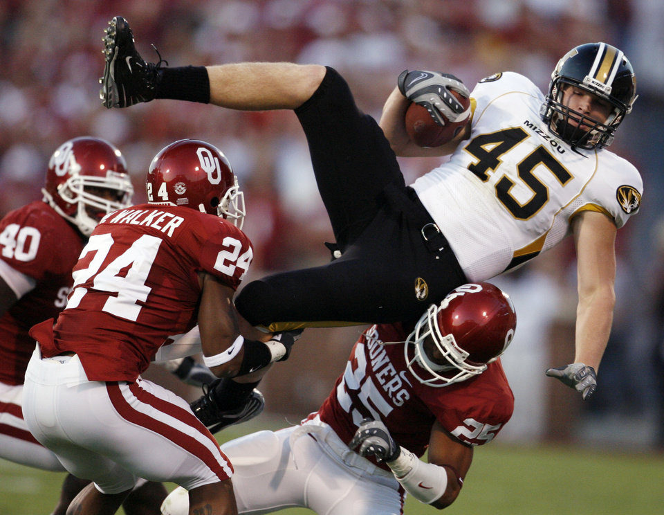 Photo - Oklahoma's Marcus Walker (24) and D.J. Wolfe (25) bring down Missouri's Chase Coffman (45) during the first half of the college football game between the University of Oklahoma Sooners (OU) and the University of Missouri Tigers (MU) at the Gaylord Family -- Oklahoma Memorial Stadium on Saturday, Oct. 13, 2007, in Norman, Okla.  By STEVE SISNEY, The Oklahoman  ORG XMIT: KOD