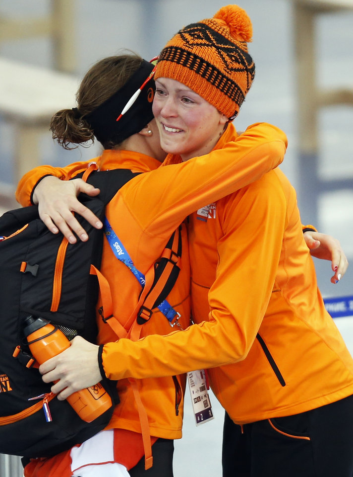 Photo - An emotional gold medallist Jorien ter Mors of the Netherlands, right, is congratulated by silver medallist country skater Ireen Wust after the women's 1,500-meter speedskating race at the Adler Arena Skating Center during the 2014 Winter Olympics in Sochi, Russia, Sunday, Feb. 16, 2014. (AP Photo/Pavel Golovkin)