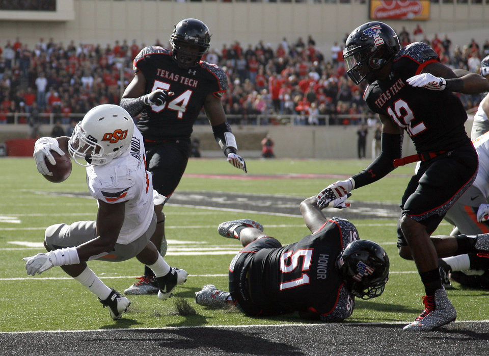 Oklahoma State Cowboys's Joseph Randle (1) scores a touchdown in front of Texas Tech's Dartwan Bush (54), Cqulin Hubert (51) and D.J. Johnson (12) during a college football game between Texas Tech University (TTU) and Oklahoma State University (OSU) at Jones AT&T Stadium in Lubbock, Texas, Saturday, Nov. 12, 2011.  Photo by Sarah Phipps, The Oklahoman  ORG XMIT: KOD