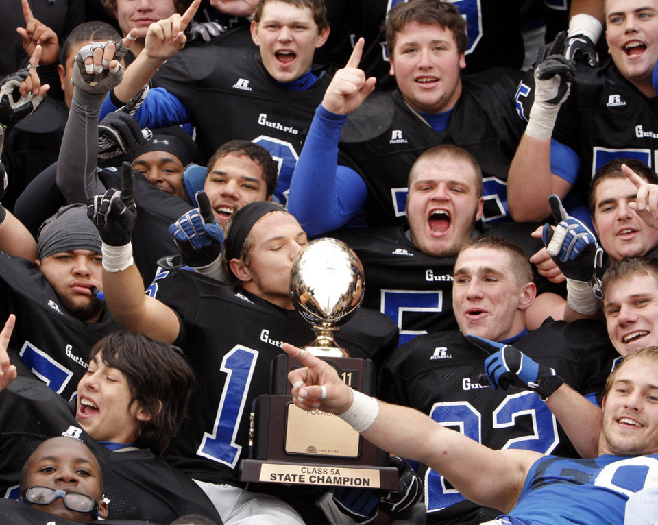 Photo - The Guthrie players pose for a photo with the gold ball championship trophy after the Class 5A high school football state championship game between Guthrie and Lawton MacArthur at Boone Pickens Stadium in Stillwater, Okla., Friday, Dec. 2, 2011. Guthrie won, 24-7. Photo by Nate Billings, The Oklahoman
