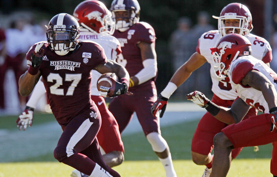 Photo -   Mississippi State running back LaDarius Perkins (27) runs past Arkansas safety Rohan Gaines (26) and linebacker Jarrett Lake (39) during the fourth quarter of an NCAA college football game in Starkville, Miss., Saturday, Nov. 17, 2012. Mississippi State won 45-14. (AP Photo/Rogelio V. Solis)