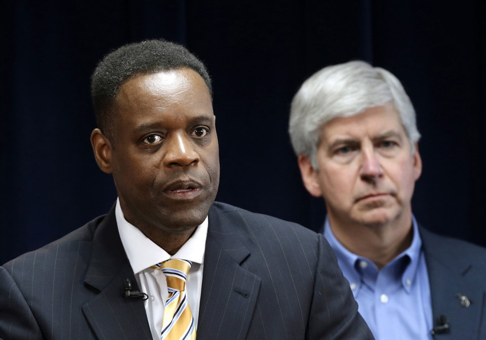 Photo - FILE - In this March 14, 2013, file photo, Detroit emergency manager Kevyn Orr, left, speaks at a news conference in Detroit as Michigan Gov. Rick Snyder, who appointed Orr, listens. The Koch Brothers' Americans for Prosperity organization is launching an effort to kill the legislative appropriation that is the key to Detroit's bankruptcy settlement. (AP Photo/Paul Sancya, File)