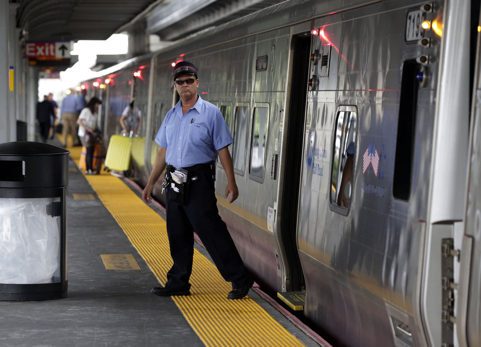 Photo - A conductor checks the platform at the Jamaica station of the Long Island Rail Road, in the Queens borough of New York, Wednesday, July 16, 2014. Negotiations aimed at avoiding a walkout at the nation's largest commuter railroad resumed Wednesday after Gov. Andrew Cuomo prodded both sides to find an agreement that would keep 300,000 daily riders from being forced to find alternate ways of getting in and out of New York City. (AP Photo/Richard Drew)