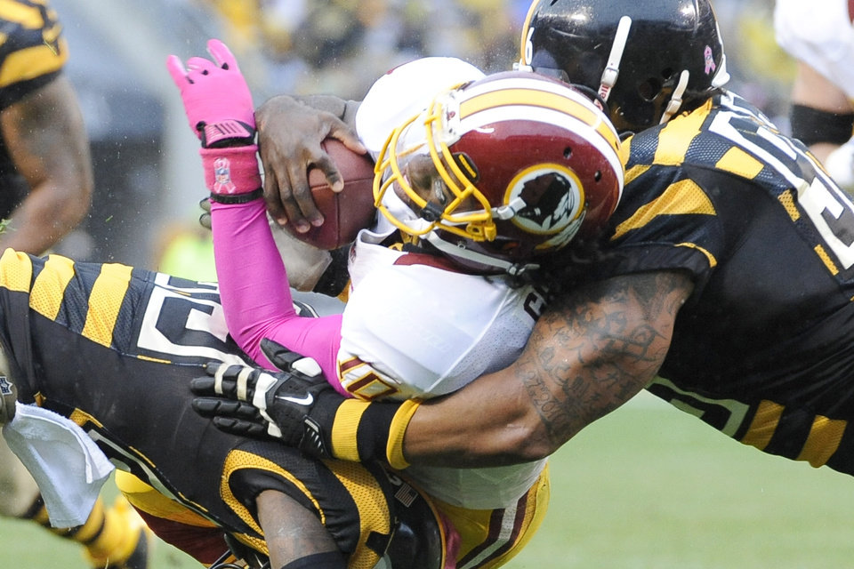 Photo -   Washington Redskins quarterback Robert Griffin III, center, is stopped by Pittsburgh Steelers nose tackle Casey Hampton, right, and cornerback Keenan Lewis (23) in the second quarter during an NFL football game on Sunday, Oct. 28, 2012, in Pittsburgh. (AP Photo/Don Wright)