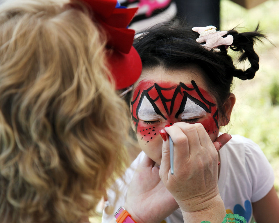Photo - Sophia Zhao, 3, has her face painted by Debbie Drain during the Festival of the Child in Yukon. Photos by Nate Billings, The Oklahoman