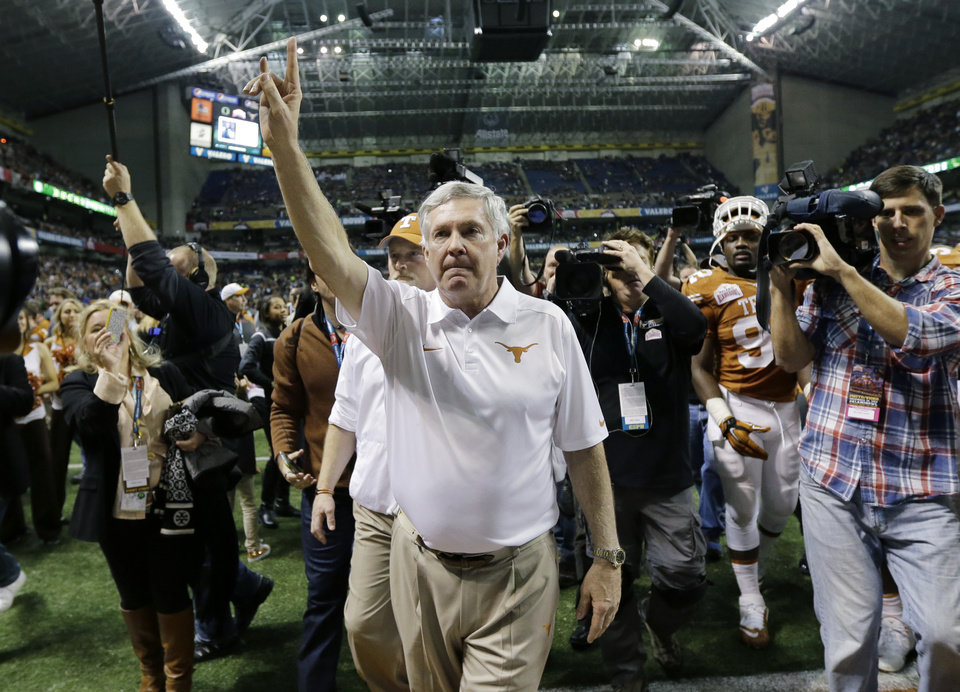 Photo - Texas coach Mack Brown, center, holds up the