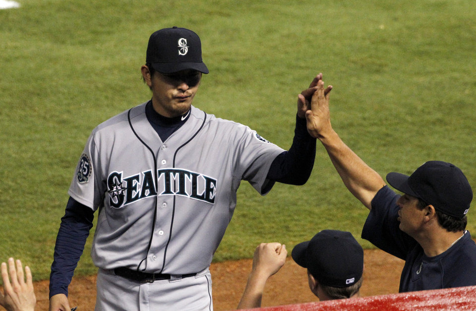 Photo -   Seattle Mariners' Hisashi Iwakuma, center, of Japan is greeted back at the dugout after being pulled in the sixth inning of a baseball game against the Texas Rangers Friday, Sept. 14, 2012, in Arlington, Texas. (AP Photo/Tony Gutierrez)