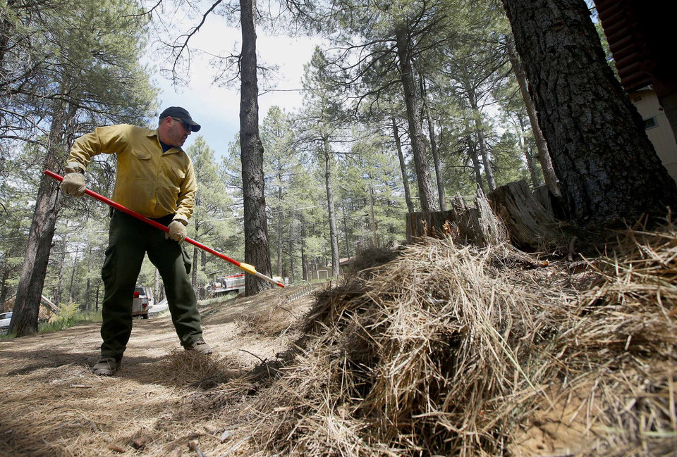Photo - John Rheinbolt, of the Western Defense Systems private contractor, works on pulling pine needles and other ground clutter away from a home as the Slide Fire burns nearby on Thursday, May 22, 2014, in Kachina Village, Ariz.   The fire, which has burned approximately 4,800 acres, is 3 to 3 1/2 miles away from the residential areas of Forest Highlands and Kachina Village, where the 3,200 residents remain under pre-evacuation warnings. (AP Photo/Ross D. Franklin)