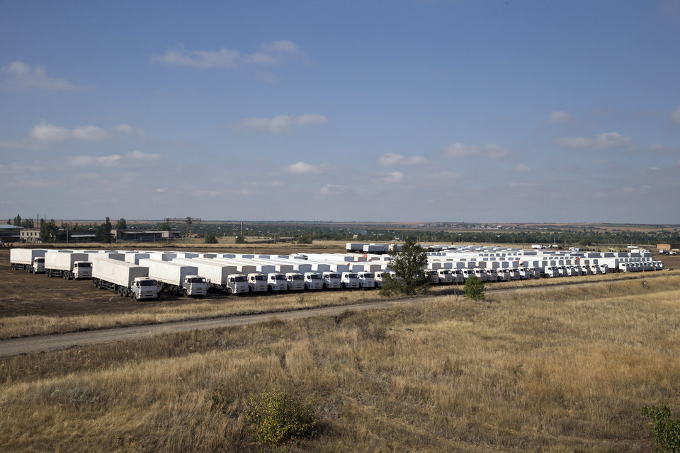 Photo - The Russian aid convoy is parked in a field about 28 kilometers (17 miles) from the Ukrainian border, near Kamensk-Shakhtinsky, Rostov-on-Don region, Russia, Wednesday, Aug. 20, 2014. Tensions in the region have been high since Russia announced plans last week to send an aid convoy of more than 200 trucks to help alleviate the unfolding humanitarian crisis in the east. The International Committee of the Red Cross, which is expected to take responsibility for the convoy when it enters Ukraine, was still awaiting security guarantees from all sides. (AP Photo/Pavel Golovkin)