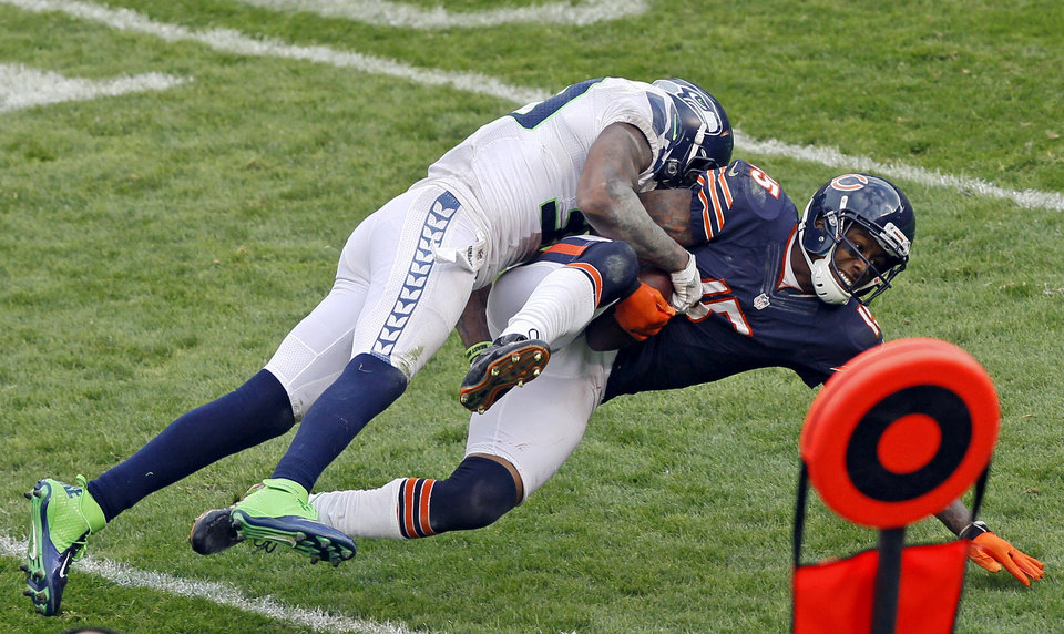 Photo - Chicago Bears wide receiver Brandon Marshall (15) is tackled by a Seattle Seahawks defender in the second half of an NFL football game in Chicago, Sunday, Dec. 2, 2012. (AP Photo/Charles Rex Arbogast)