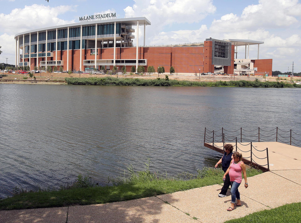 Photo - FILE - In this July 2, 2014, file photo, people stroll along the river walk across from the new McClane Stadium at Baylor University in Waco, Texas. The $260 million stadium located near campus on the Brazos river debuts at the end of the month and replaces the  64-year-old Floyd Casey Stadium. (AP Photo/Waco Tribune Herald, Jerry Larson, File)