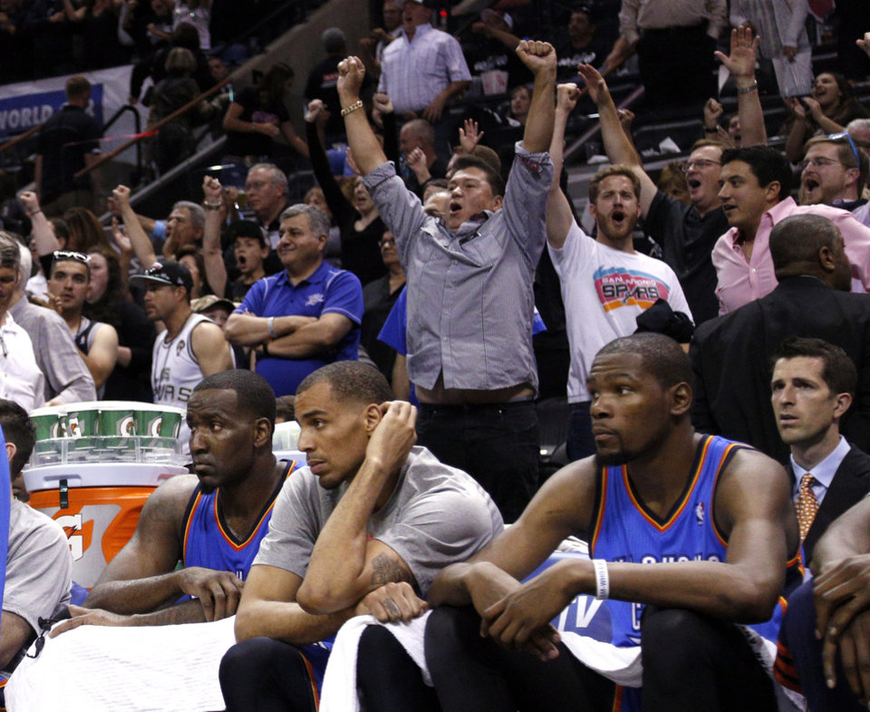 Photo - Serge Ibaka (9), Thabo Sefolosha (25) and Kevin Durant (35) watch the final second of the game as fans celebrate during Game 1 of the Western Conference Finals in the NBA playoffs between the Oklahoma City Thunder and the San Antonio Spurs at the AT&T Center in San Antonio, Monday, May 19, 2014. Photo by Sarah Phipps, The Oklahoman