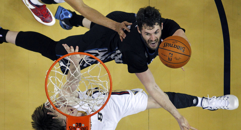 Photo - Minnesota Timberwolves power forward Kevin Love, top, goes to the basket against New Orleans Pelicans small forward Luke Babbitt (8) in the second half of an NBA basketball game in New Orleans, Friday, Feb. 7, 2014. The Pelicans won 98-91. (AP Photo/Gerald Herbert)
