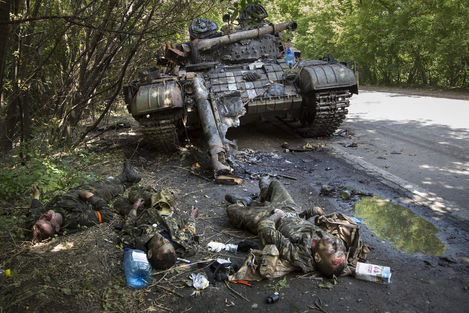 Photo - EDITORS NOTE GRAPHIC CONTENT - Bodies of crew members lie next to a destroyed Ukrainian tank in the northern outskirts of city of Donetsk, eastern Ukraine Tuesday, July 22, 2014. The soldiers were reportedly killed in fighting between rebels and government forces Monday. (AP Photo/Dmitry Lovetsky)