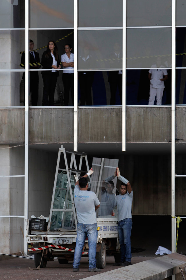 Photo - Workers unload a sheet of window glass at the Foreign Ministry in Brasilia, Brazil, Friday, June 21, 2013. The workers are replacing windoows that were broken by anti-government protestors who unsuccessfully attempted to invade the building Thursday evening. President Dilma Rousseff called an emergency meeting of her top Cabinet members Friday morning, more than a week after the protests began. (AP Photo/Eraldo Peres)