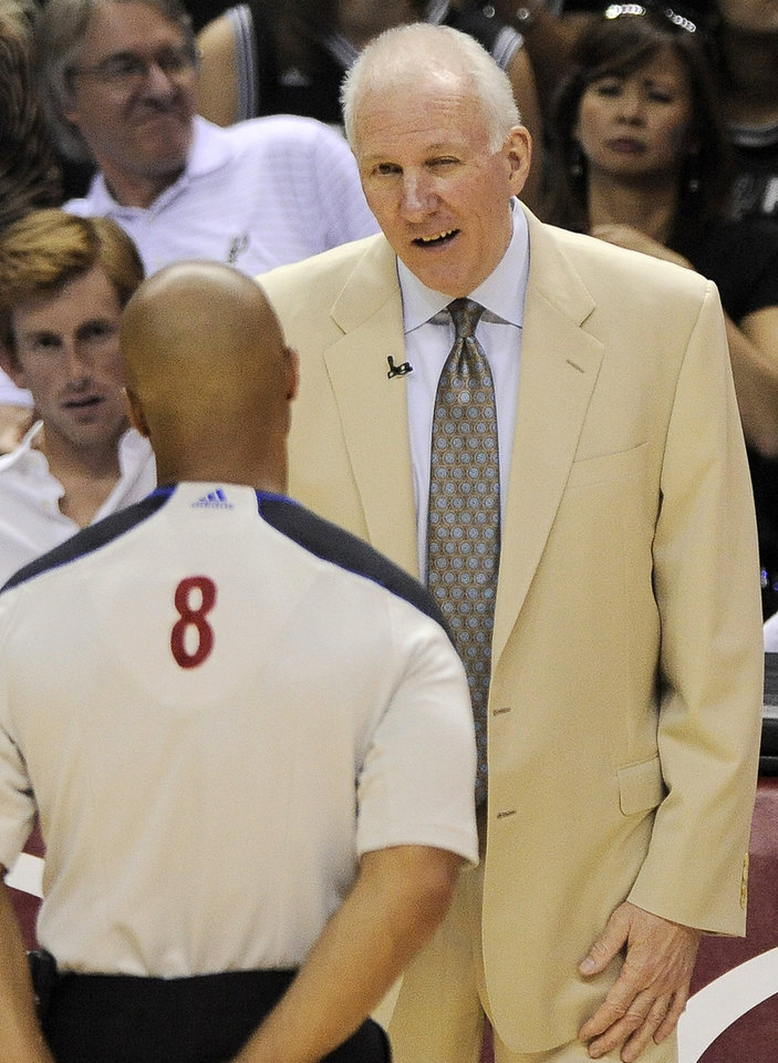 Photo - San Antonio Spurs head coach Gregg Popovich, right, talks with referee Marc Davis during the first half of Game 1 of the Western Conference final NBA basketball playoff series against the Memphis Grizzlies, Sunday, May 19, 2013, in San Antonio. San Antonio won 105-83. (AP Photo/Darren Abate)