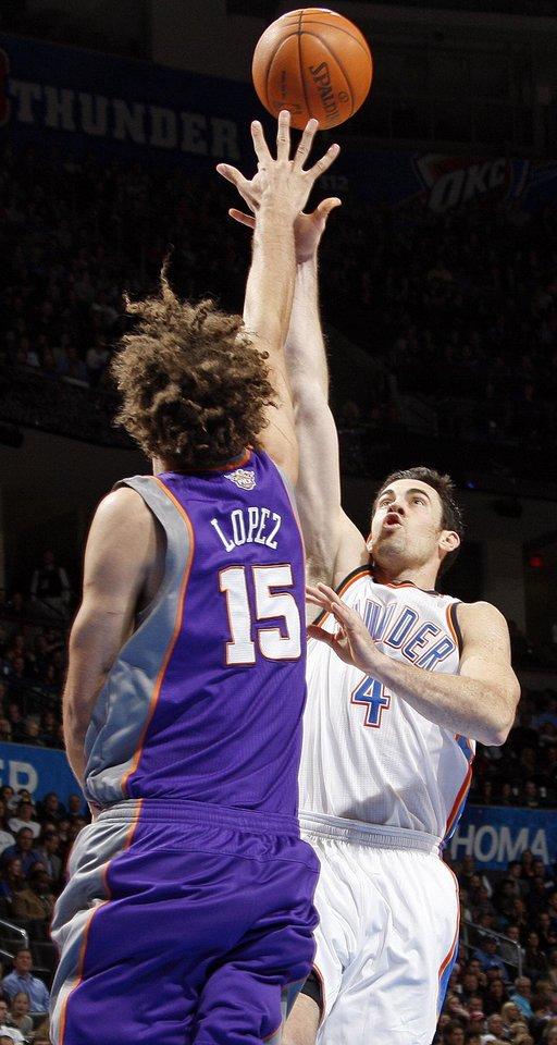 Photo - Oklahoma City's Nick Collison (4) shoots over Robin Lopez (15) of Phoenix during the NBA basketball game between the Oklahoma City Thunder and Phoenix Suns at Chesapeake Energy Arena in Oklahoma City, Saturday, Dec. 31, 2011. Photo by Nate Billings, The Oklahoman