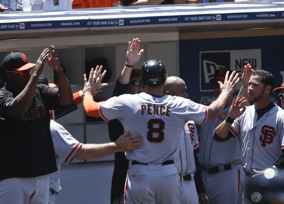 Photo - San Francisco Giants' Hunter Pence is greeted at the dugout  after scoring in the third inning against the San Diego Padres in a baseball game Sunday, July 6, 2014, in San Diego.  (AP Photo/Lenny Ignelzi)