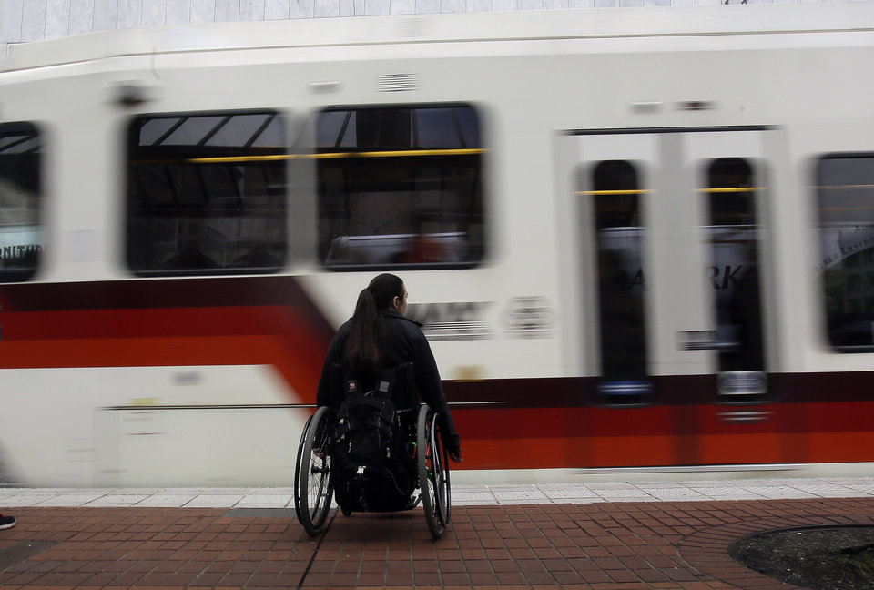 Photo - A rider waits to board an incoming MAX train in Portland, Ore., Monday, March 10, 2014.  While use of buses, trains and subways is on the rise in many cities across America, ridership in the Portland area's much touted system has actually fallen off, according to new data released by the American Public Transportation Association. (AP Photo/Don Ryan)