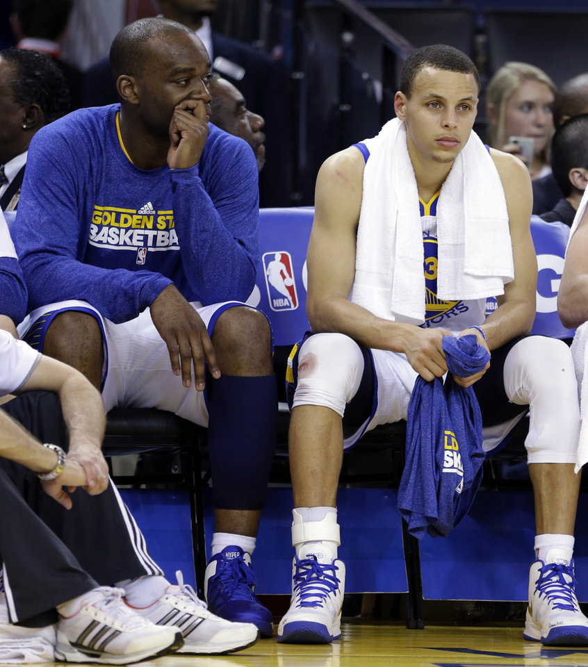 Golden State Warriors' Carl Landry, left, and Stephen Curry watch from the bench during the second half of an NBA basketball game against the Oklahoma Thunder Thursday, April 11, 2013, in Oakland, Calif. (AP Photo/Ben Margot)