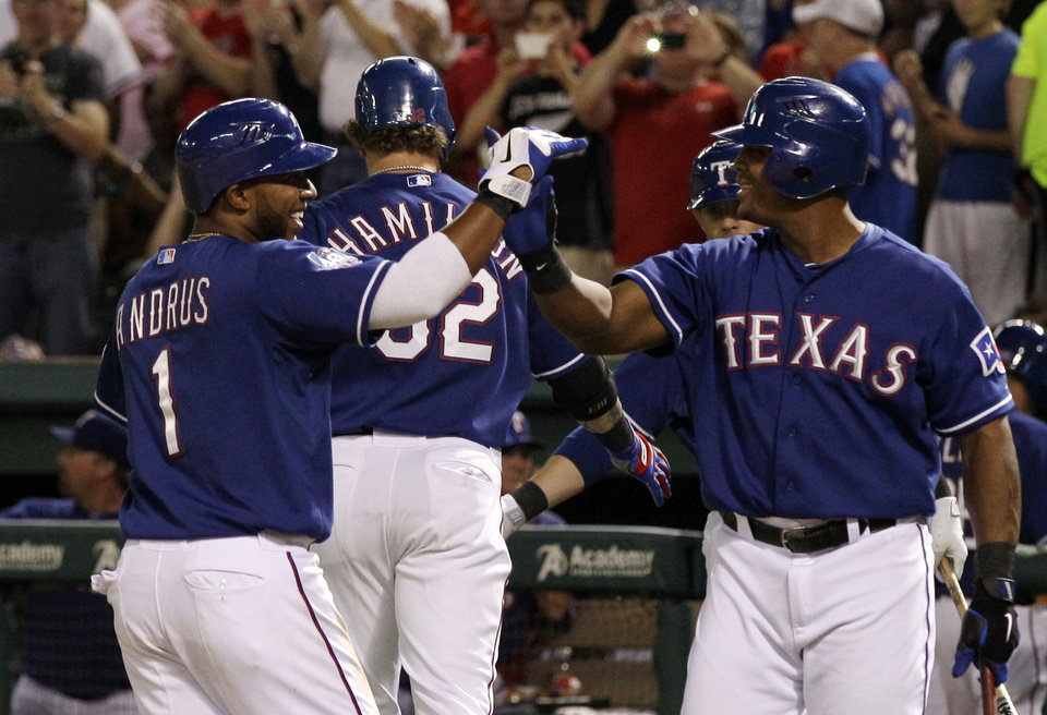 Photo -   Texas Rangers' Elvis Andrus, left, and Adrian Beltre, right, celebrate after Andrus scored on a two-run home run by Josh Hamilton, rear, in the fifth inning of a baseball game against the Tampa Bay Rays, Friday, April 27, 2012, in Arlington, Texas. The shot came off a pitch from Rays starter James Shields. (AP Photo/Tony Gutierrez)