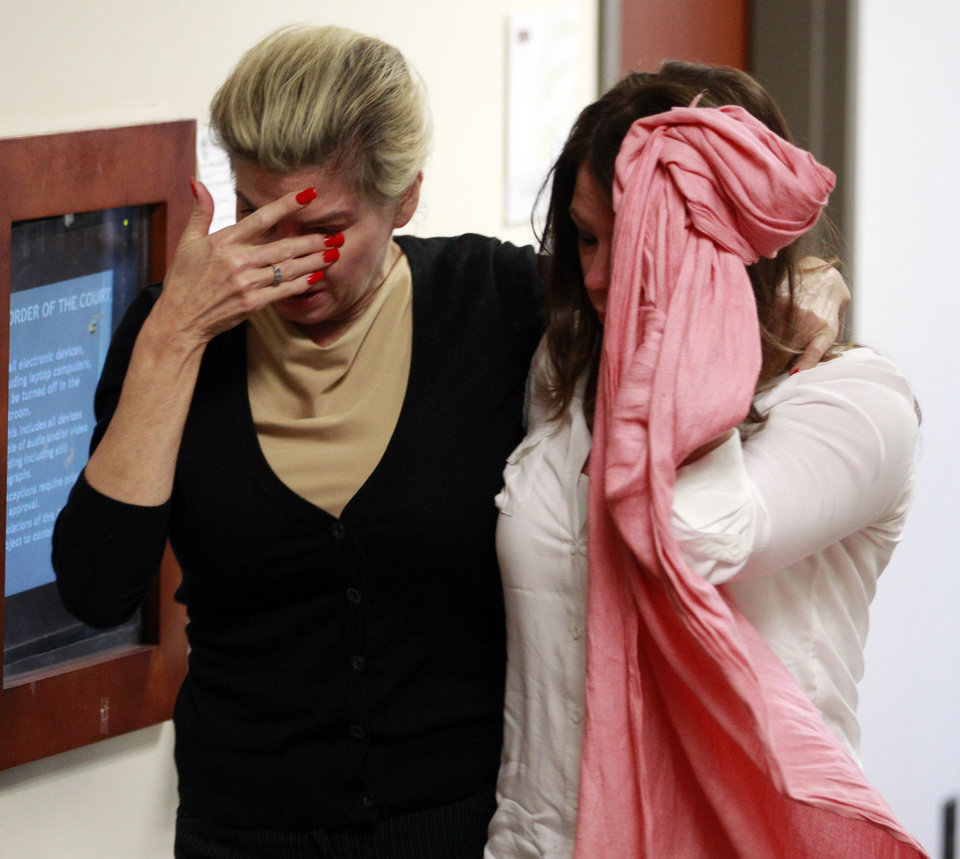 Two unidentified women hide their faces as they leave the courtroom  in the case of  Aurora theater shooting suspect James Holmes in Centennial, Colo., on Monday, April 1, 2013, after hearing that the prosecution will seek the death penalty in the case against Holmes. (AP Photo/Brennan Linsley)