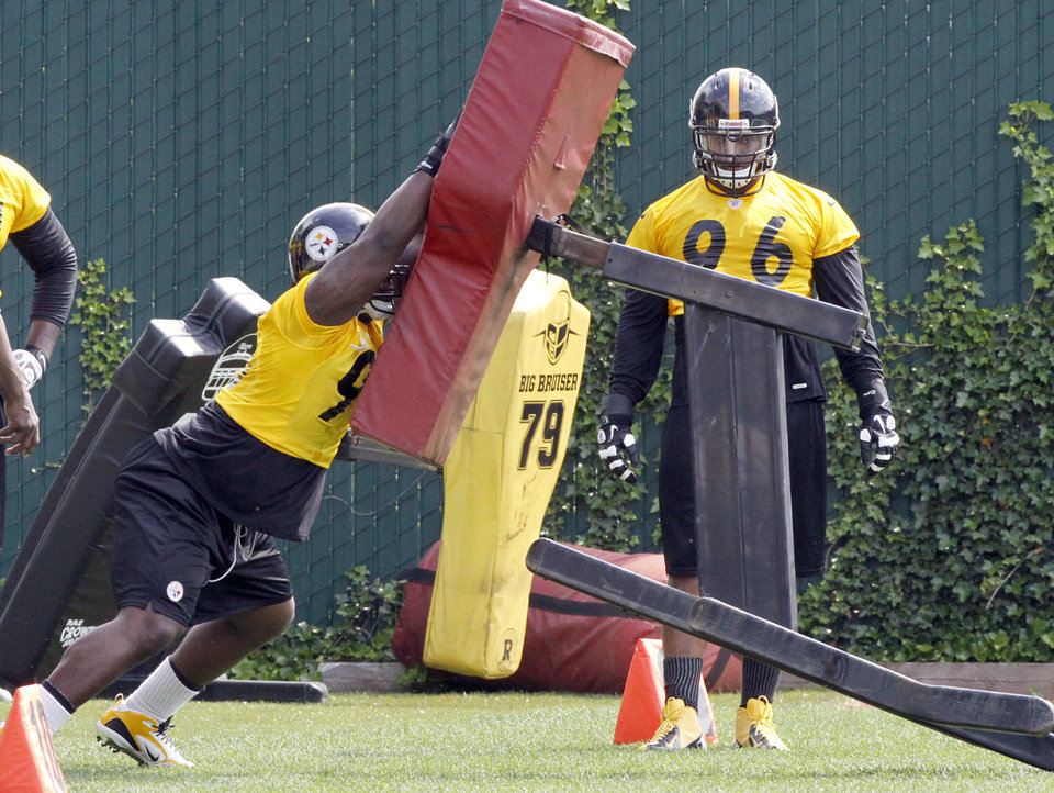 Photo -   Pittsburgh Steelers defensive tackle Steve McLendon, left, hits a blocking sled as Ziggy Hood (96) watches during the first day of NFL football practice at the team's training facility on Tuesday, May 22, 2012 in Pittsburgh. (AP Photo/Keith Srakocic)