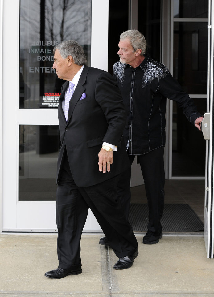 Photo - Attorney James Voyles, left and Indianapolis Colts owner Jim Irsay leave the Hamilton County Jail in Indianapolis, Monday, March 17, 2014. Irsay was released from jail Monday after being held overnight following a traffic stop in which police said he failed sobriety tests and had multiple prescription drugs inside his vehicle. Irsay was pulled over late Sunday after he was spotted driving slowly near his home in suburban Carmel, stopping in the roadway and failing to use a turn signal.  (AP Photo/Alan Petersime)