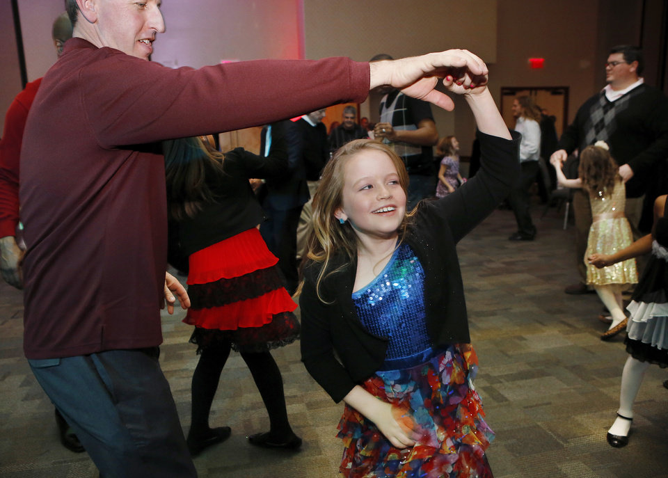 Meghan McGregor, 9, is swung in a circle on the dance floor by her dad, Tim McGregor of Midwest City. Midwest City Parks and Recreation Department hosted the city's annual Daddy-Daughter Dance that featured three 90-minute dance sessions at the Reed Center on Saturday, Feb. 16, 2013.    Photo by Jim Beckel, The Oklahoman