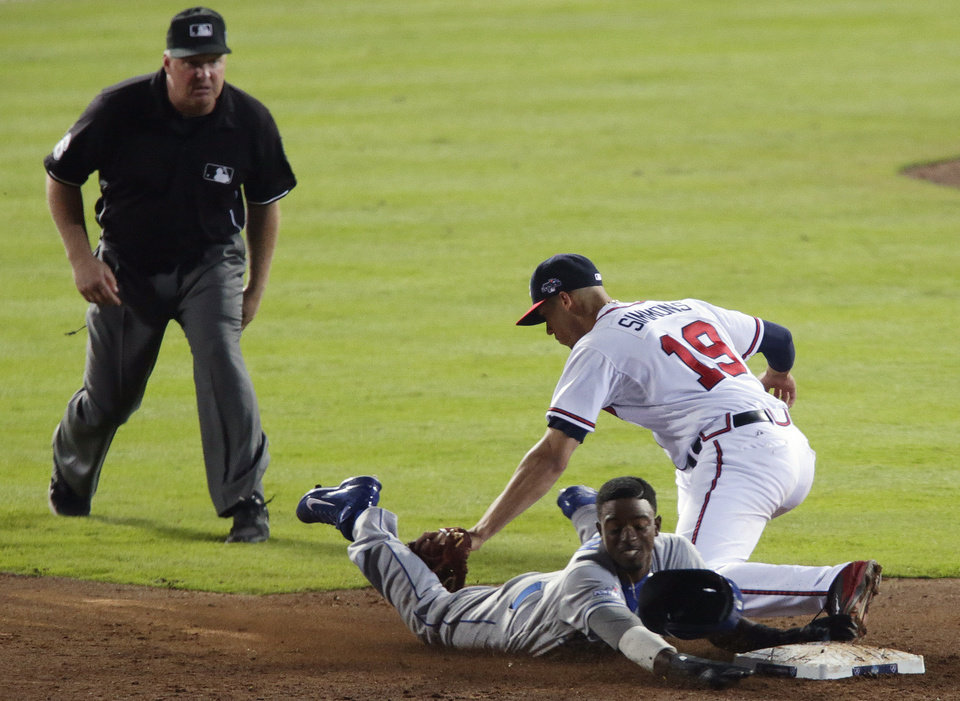 Photo - As umpire Mike Muchlinski, left, watches, Los Angeles Dodgers' Dee Gordon, bottom right, tries to steal second base as Atlanta Braves shortstop Andrelton Simmons (19) makes the tag in the ninth inning of Game 2 of the National League division series on Friday, Oct. 4, 2013, in Atlanta. The Braves won 4-3. (AP Photo/Dave Martin)
