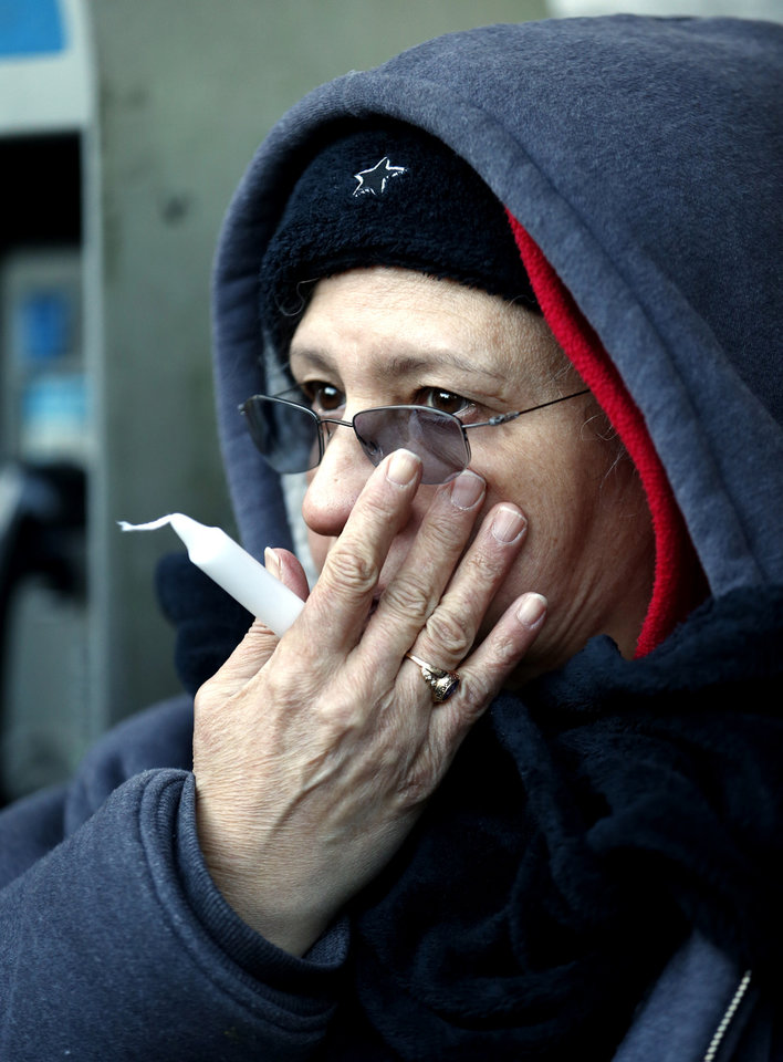 Photo - A woman holds a candle while listening to prayers during a vigil for the victims of an explosion, Thursday, March 13, 2014 in New York. Rescuers working amid gusty winds, cold temperatures and billowing smoke pulled four additional bodies from the rubble of two New York City apartment buildings, raising the death toll to at least seven from a gas leak-triggered explosion that reduced the area to a pile of smashed bricks, splinters and mangled metal. The explosion Wednesday morning in Manhattan's East Harlem injured more than 60 people. (AP Photo/Julio Cortez)