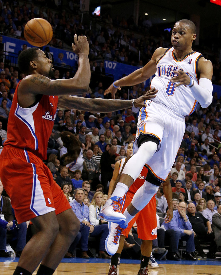 Photo - Oklahoma City's Russell Westbrook (0) passes the ball over the Clippers DeAndre Jordan (6) during an NBA basketball game between the Oklahoma City Thunder and the Los Angeles Clippers at Chesapeake Energy Arena in Oklahoma City, Wednesday, Nov. 21, 2012. Photo by Bryan Terry, The Oklahoman