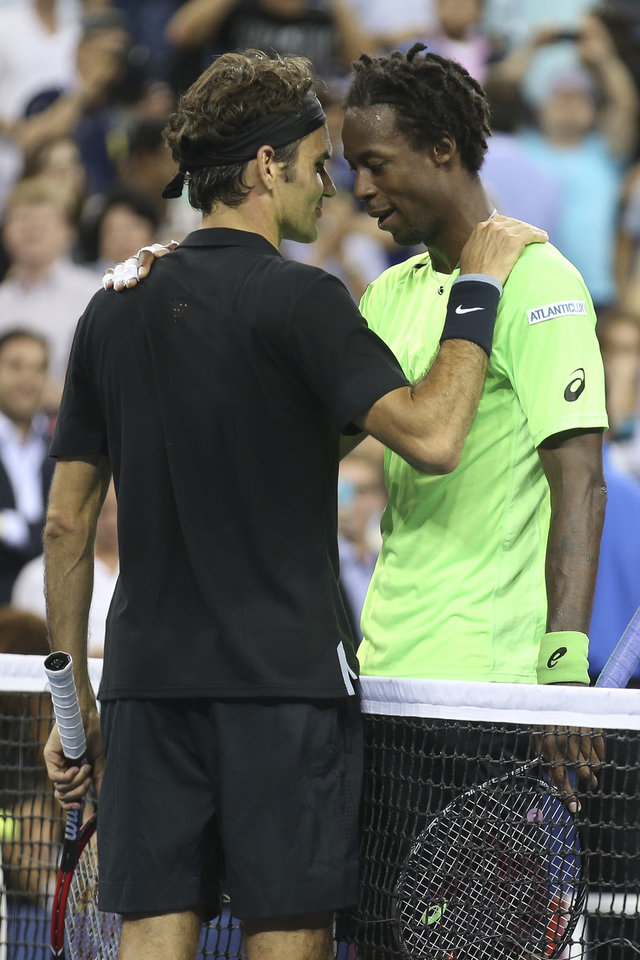 Photo - Gael Monfils, right, of France, meets at the net with Roger Federer, of Switzerland, after their quarterfinal at the U.S. Open tennis tournament, Thursday, Sept. 4, 2014, in New York. Federer won 4-6, 3-6, 6-4, 7-5, 6-2. (AP Photo/John Minchillo)