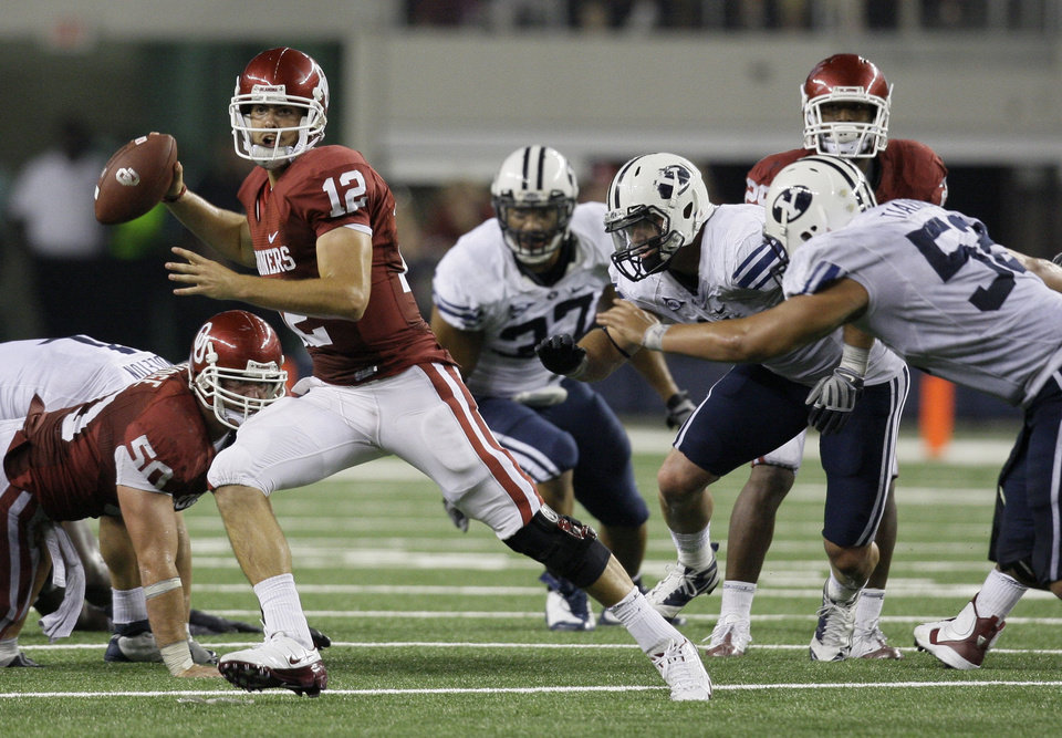 Photo - OU: University of Oklahoma quarterback Landry Jones (12) is pressured out of the pocket by BYU defenders in the second half of an NCAA college football game, Saturday, Sept. 5, 2009, in Arlington, Texas. BYU won 14-13. (AP Photo/Tony Gutierrez) ORG XMIT: DNS119