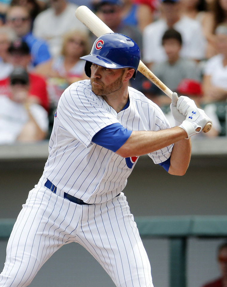 Photo - Chicago Cubs' Nate Schierholtz hits against the Los Angeles Angels during the first inning of a spring training baseball game, Tuesday, March 25, 2014, in Mesa, Ariz. (AP Photo/Matt York)